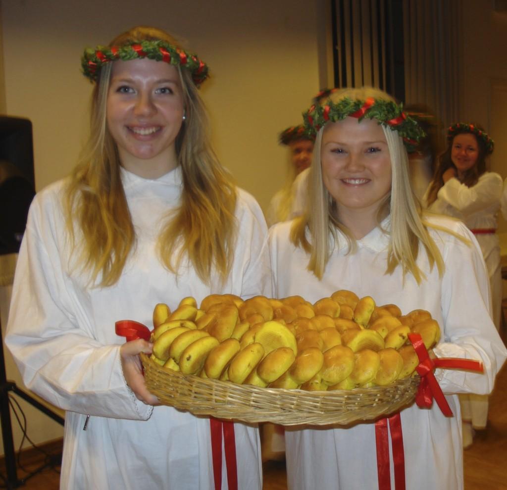 Couronnée de feuillage, les demoiselles d'honneur de Lucia, distribuent les petites pains au safran, les lussebulle